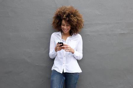 Portret van gelukkige jonge vrouw luisteren naar muziek op mobiele telefoon Stockfoto