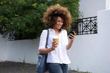 femme africaine: Portrait de jeune femme africaine avec les cheveux boucl�s marchant avec un t�l�phone mobile