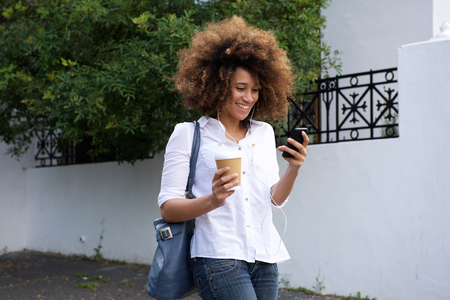charming woman: Portrait of young african woman with curly hair walking with mobile phone