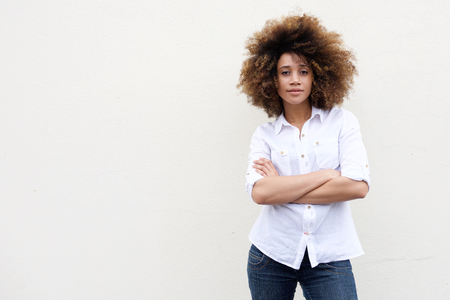 Portrait of a cool young african american woman with curly hair standing against white background