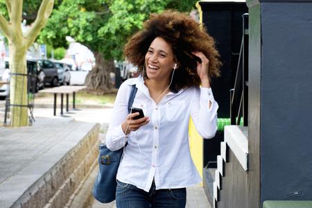Portrait de jeune femme souriante avec des écouteurs et téléphone intelligent