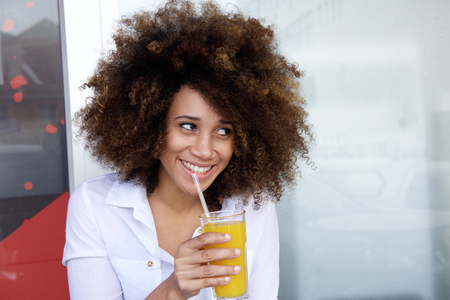 a straw: Portrait of a smiling african american woman drinking juice
