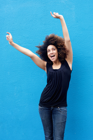 happy african woman: Portrait of young woman smiling with arms raised