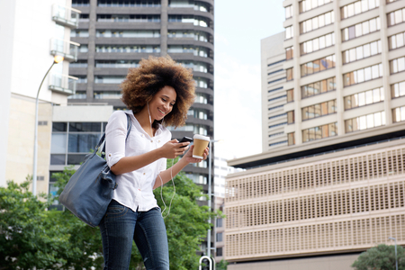 lady on phone: Portrait of young african woman walking and looking at mobile phone Stock Photo