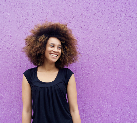 Portrait of laughing young woman standing against purple background Standard-Bild
