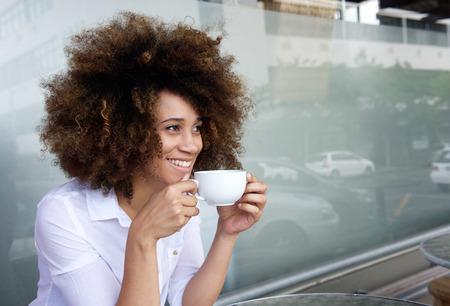 Portret van lachende Afro-Amerikaanse vrouw zitten met een kopje koffie