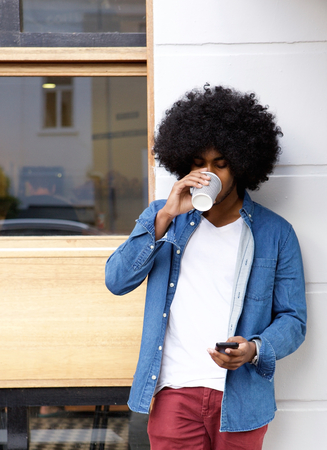 jovenes estudiantes: Retrato de un individuo fresco beber caf� y utilizando el tel�fono celular