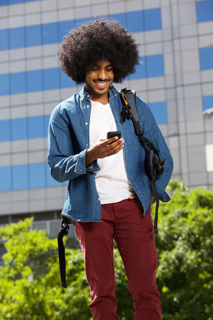 african american man: Portrait of a cool travel guy walking with mobile phone Stock Photo