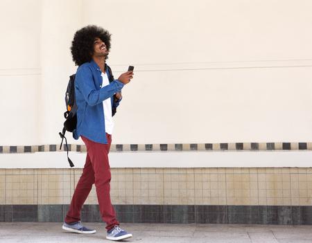 cuerpo hombre: Retrato de cuerpo entero de un hombre negro joven sonriente caminando con bolsa y el teléfono móvil