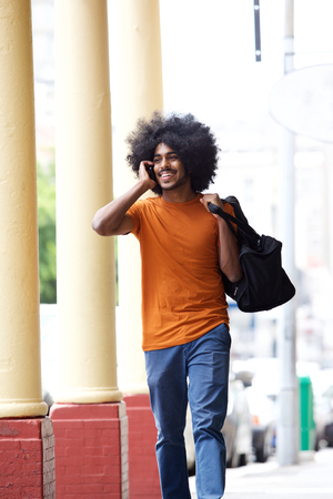 city people: Portrait of a cool guy talking on cell phone carrying bag in town Stock Photo