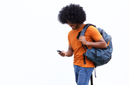 black guy: Portrait of a smiling young man walking with bag and mobile phone