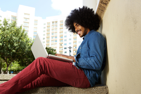 Side portrait of a smiling male student sitting outside working on laptop Stock Photo