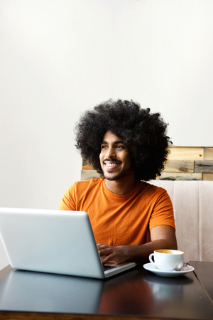 cool guy: Portrait of a smiling man sitting at table with laptop Stock Photo