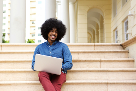 cool guy: Portrait of a cool black guy sitting outside using laptop