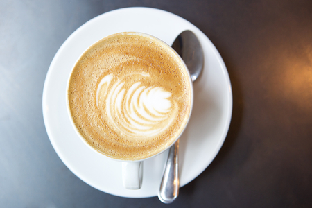 high angle shot: Cup of coffee on saucer with spoon from above