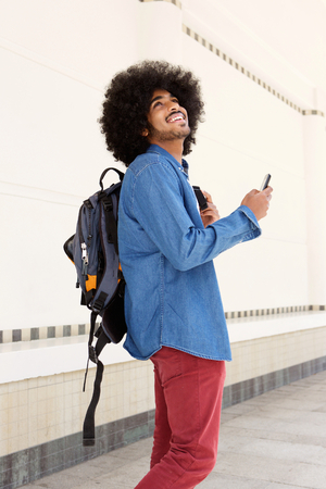 african american man: Portrait of a happy man walking with bag and mobile phone Stock Photo