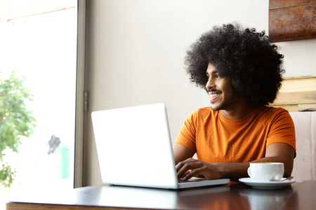 man studying: Portrait of a happy student sitting at table with laptop Stock Photo