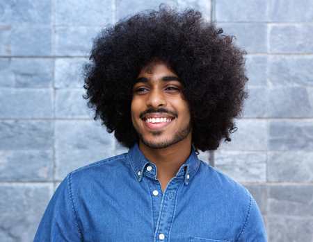 hair man: Close up portrait of a cool young black guy smiling with afro