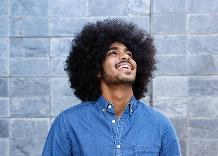 black guy: Close up portrait of young black guy laughing and looking up Stock Photo