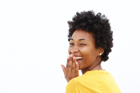 excitement: Portrait of happy african woman covering her mouth and laughing against white background Stock Photo