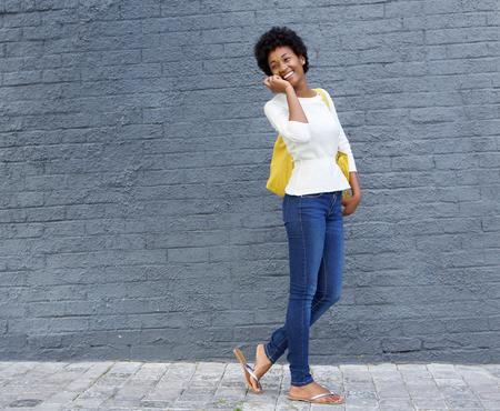 mujeres africanas: Retrato de un joven afroamericano mujer caminando y hablando por teléfono celular