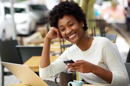 Portret van een lachende jonge Afro-Amerikaanse vrouw zit bij koffie met mobiele telefoon