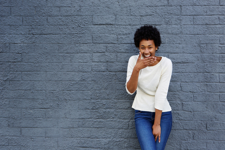 people laughing: Portrait of happy african woman covering her mouth and laughing against a gray wall