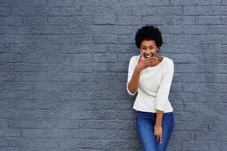 reir: Retrato de la mujer africana feliz que cubre la boca y se ríe contra una pared gris