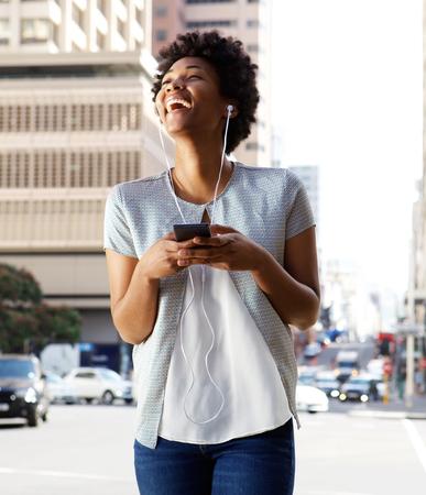 Portret van jonge Afrikaanse vrouw genieten van het luisteren van muziek op haar mobiele telefoon Stockfoto