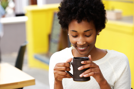 warm drink: Closeup portrait of happy young black woman drinking coffee Stock Photo