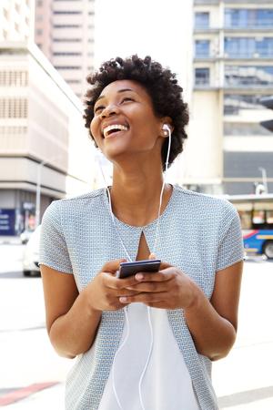 mujeres felices: Retrato de una música que escucha de la mujer africana joven hermosa con los auriculares en calle de la ciudad