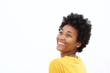 Close-up portret van lachende jonge zwarte vrouw weg te kijken tegen een witte achtergrond Stockfoto