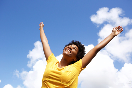Portrait of cheerful young woman standing outside with her hands raised towards sky Standard-Bild