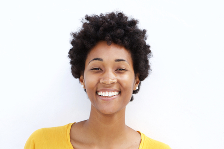 Closeup portrait of smiling young black woman against white background Stock Photo