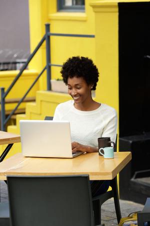 femme africaine: Portrait d'une jeune femme heureuse africain assis à un café en plein air travaillant sur un ordinateur portable. Banque d'images