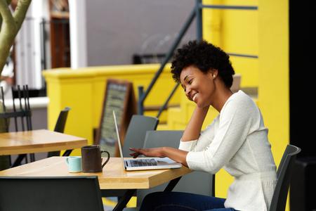 Portret van een gelukkige jonge Afrikaanse vrouw die ontspannen in de buitenlucht cafe en met behulp van een laptop