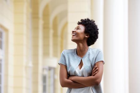 jeune fille: Portrait d'une jeune femme africaine souriant debout en plein air avec ses bras crois�s et regarder loin Banque d'images
