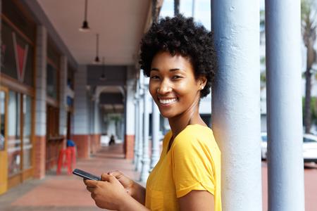 modelos negras: Retrato de una mujer africana joven atractiva que sostiene un teléfono móvil que se inclina al aire libre pilar Foto de archivo