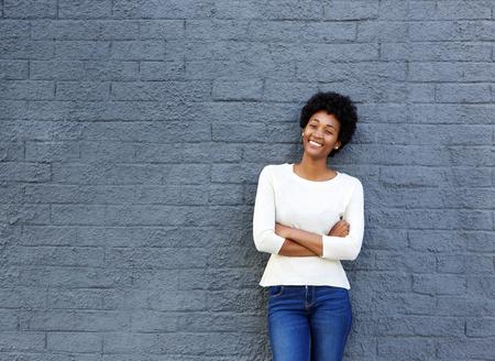 Portret van vertrouwen jonge Afrikaanse vrouw die zich tegen een grijze muur