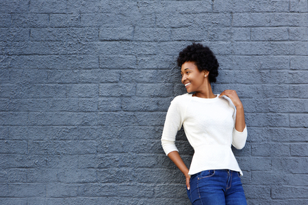 mujer alegre: Portrait of happy african woman standing against a gray wall and looking away Foto de archivo
