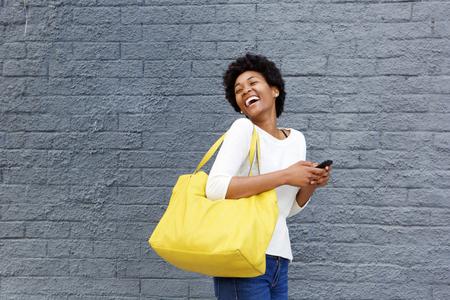 Portret van een lachende jonge Afrikaanse vrouw met een mobiele telefoon weg te kijken
