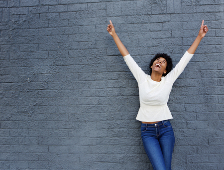 Porträt einer fröhlichen afrikanischen Frau mit erhobenen Händen nach oben zeigend