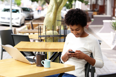 mobile internet: Portrait of african woman using mobile phone at an outdoor cafe with laptop and cup of coffee on table Stock Photo