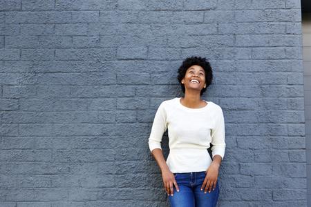 Portret van een glimlachende jonge zwarte vrouw die zich met witte sweater Stockfoto