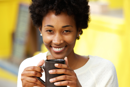 african coffee: Close up portrait of a beautiful african american woman smiling with cup of a coffee