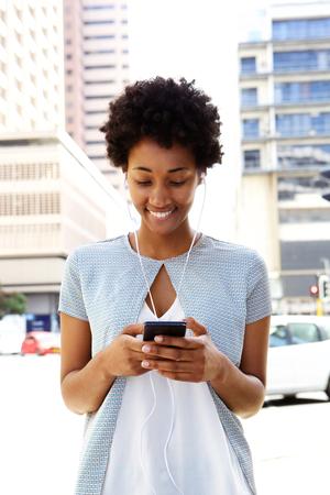 mujer alegre: Retrato de mujer joven que llevaba los auriculares que escucha la música en el teléfono móvil
