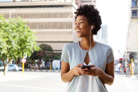personas escuchando: Retrato de la señora joven alegre en la calle de la ciudad escuchando música en su teléfono móvil
