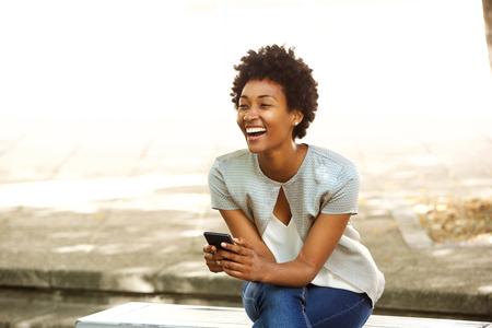 riendo: Retrato de la mujer africana joven sonriendo mientras está sentado fuera en un banco que sostiene el teléfono móvil