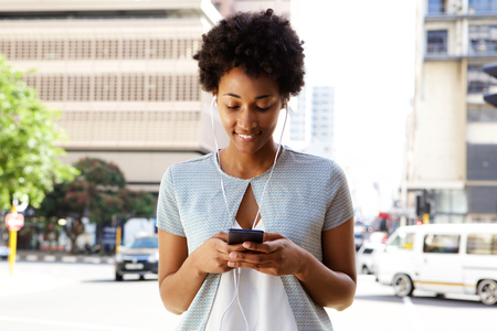 Portrait of young black woman listening to music on her cell phone outside in the city