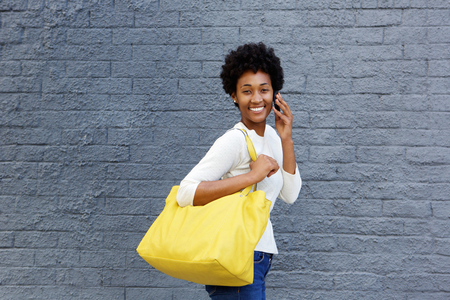Portrait of an attractive young woman with bag walking and talking on mobile phone